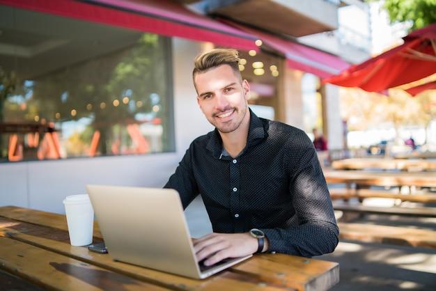 コーヒーショップに座っている間彼のラップトップに取り組んでいる青年実業家の肖像画。技術とビジネスの概念。