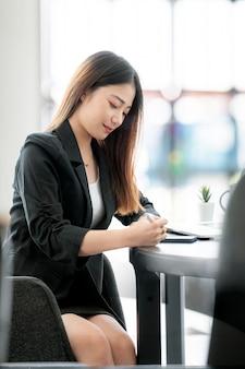 Портрет молодой предприниматель в черном костюме, работающих на ее офисном столе, вертикальный вид.