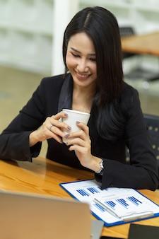 사무실에서 노트북을 통해 온라인 회의를 하는 동안 커피를 들고 있는 젊은 사업가 관리자의 초상화