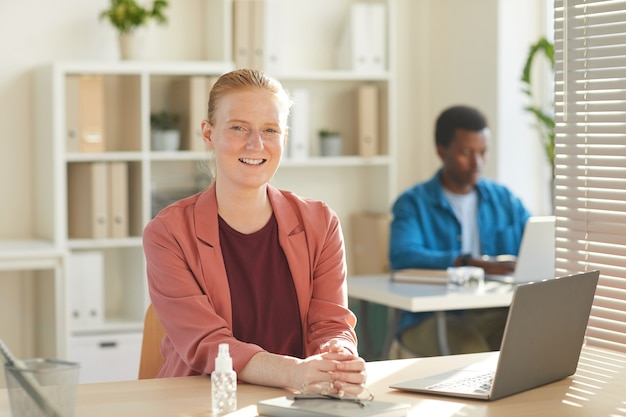 Портрет молодой деловой женщины, улыбающейся, работающей за столом в офисе с дезинфицирующим средством для рук на столе