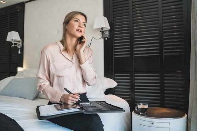 Портрет молодой коммерсантки разговаривает по телефону в гостиничном номере. концепция деловых поездок.