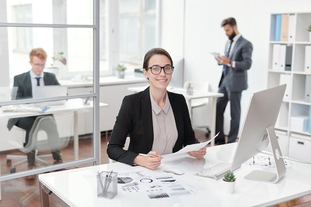 Портрет молодой деловой женщины в очках, улыбаясь, сидя за столом в офисе, бухгалтера или менеджера концепции