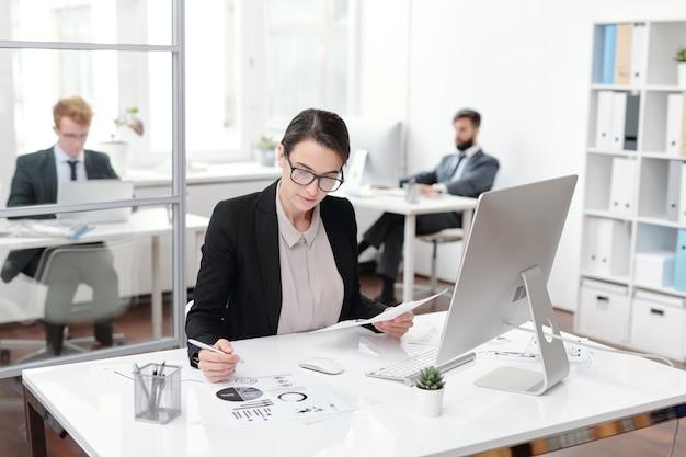 Портрет молодой бизнес-леди в очках, делая заметки во время работы за столом в офисе, бухгалтера или менеджера концепции