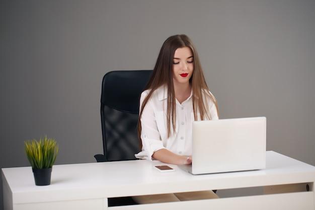 Портрет молодой предприниматель носить белую рубашку, сидя в современном офисе с ноутбуком.