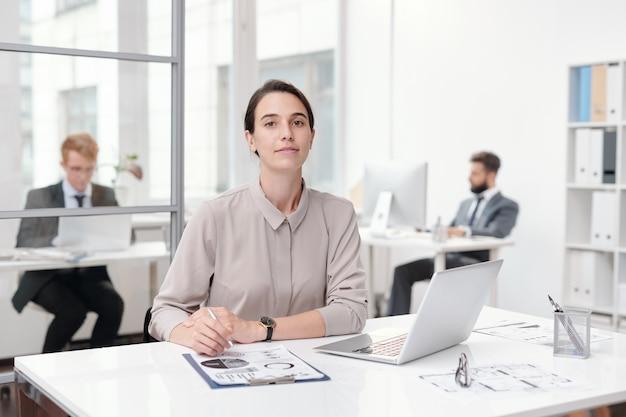 Портрет молодой деловой женщины, сидя на рабочем месте в офисе, копией пространства
