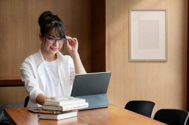 Портрет молодой коммерсантки рукой, касающейся ее очков и работы на компьютере, сидя за своим офисным столом.