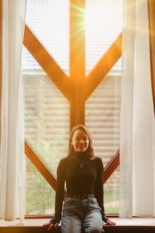 Портрет молодой деловой женщины с ноутбуком и телефоном в окне гостиной в загородном доме. женщина-трудоголик в домашней повседневной одежде, работает в отпуске. творческое вдохновение и бизнес