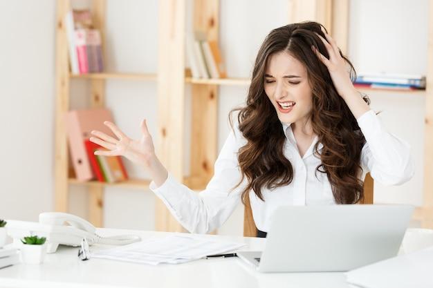 Портрет молодой деловой женщины, работающей в своем офисе с серьезным выражением лица с отчетом о документе