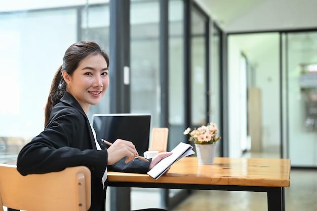 Портрет молодой коммерсантки, написание отчета в тетрадь при использовании портативного компьютера в ее офисе.