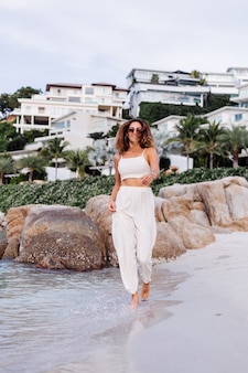 若い穏やかな幸せな白人の肖像画は、日没時に岩の多い熱帯のビーチで一人で設定された作物キャミトップとパンツのスリムな女性にフィットします