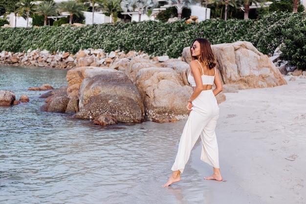 일몰 바위 열 대 해변에서 혼자 설정 작물 캐미 탑과 바지에 젊은 진정 행복 백인 맞는 슬림 여자의 초상화