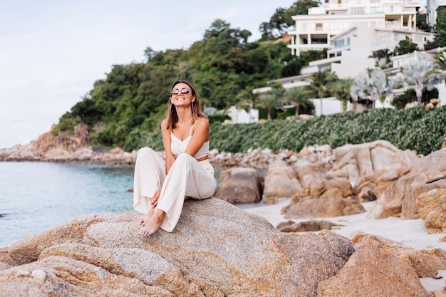 若い穏やかな幸せな白人の肖像画は、クロップキャミトップとパンツセットのスリムな女性が日没時に岩の多い熱帯のビーチに一人で座っています