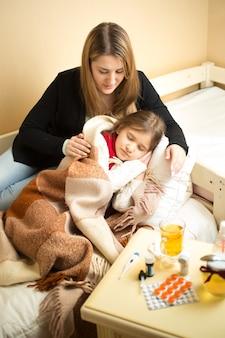 Портрет молодой заботливой матери, обнимающей больную девушку, лежащую в постели