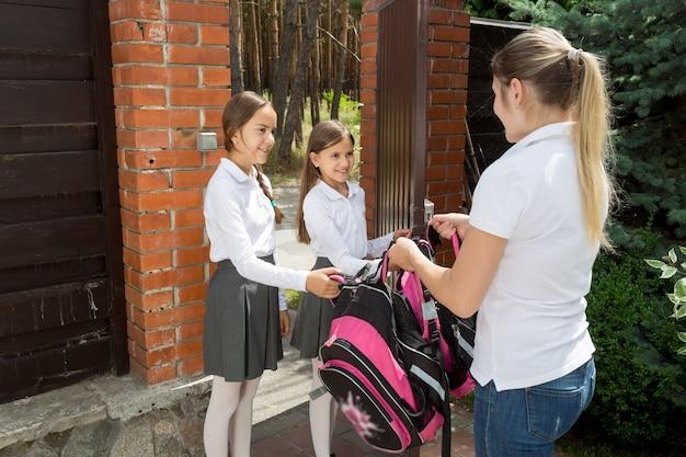 朝、学校に娘を見送る若い思いやりのある母親の肖像画