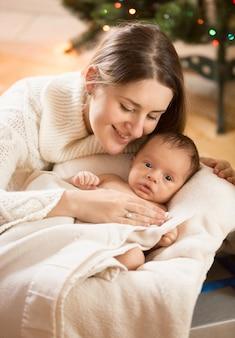 신생아 바구니에 누워있는 젊은 돌보는 어머니의 초상화