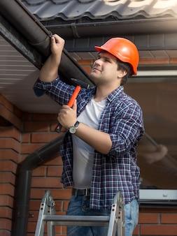 Портрет молодого плотника в каске, осматривающего крышу дома