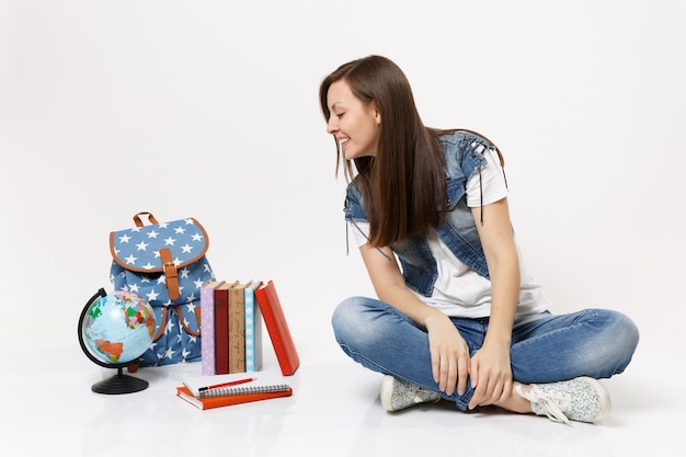 데님 옷을 입고 앉아 있는 캐주얼한 젊은 여성 학생의 초상화, 지구본, 배낭, 고립된 학교 책