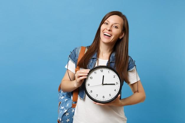 Портрет молодого случайного смеющегося приятного студента женщины в футболке, джинсовой одежде с рюкзаком, держащим будильник, изолированный на синем фоне. обучение в университете. скопируйте место для рекламы.