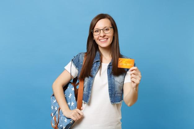 Портрет молодого случайного улыбающегося привлекательного студента женщины в джинсовой одежде, очках с рюкзаком, держащим кредитную карту, изолированную на синем фоне. образование в концепции колледжа университета средней школы.