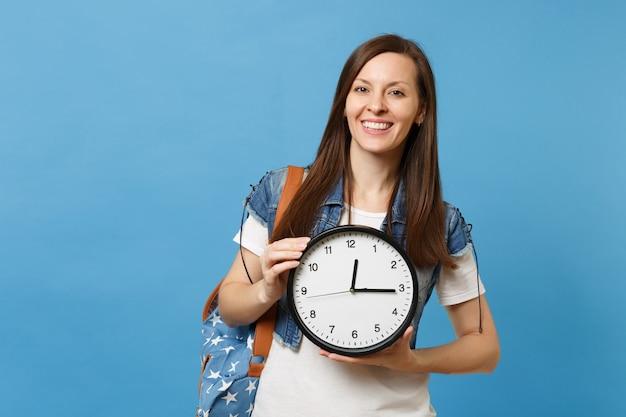 Портрет молодого случайного улыбающегося привлекательного студента женщины в футболке, джинсовой одежде с рюкзаком держит будильник, изолированный на синем фоне. обучение в средней школе. скопируйте место для рекламы.