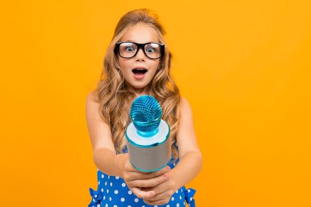 Портрет молодой кавказской девушки с длинными светлыми волосами в черных очках с микрофоном перебивает и улыбается