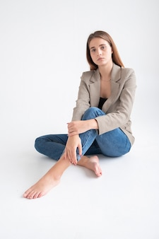 ブルージーンズ、白い背景の上のスタジオに座っているスーツのジャケットの長い茶色の髪を持つ若い白人の魅力的な女性の肖像画。床に足を組んで素足でポーズをとるやせっぽちのきれいな女性
