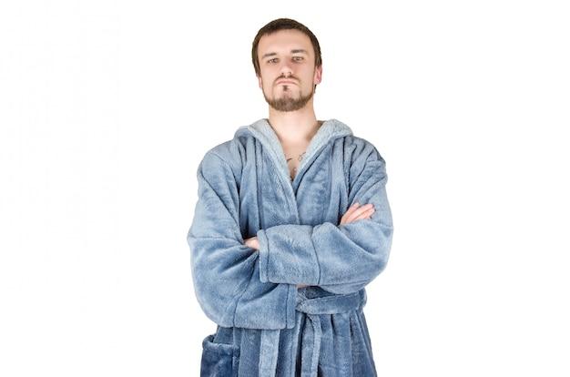 白い背景に分離された交差の手で青いバスローブで若い白人のひげを生やした誇り高い男の肖像