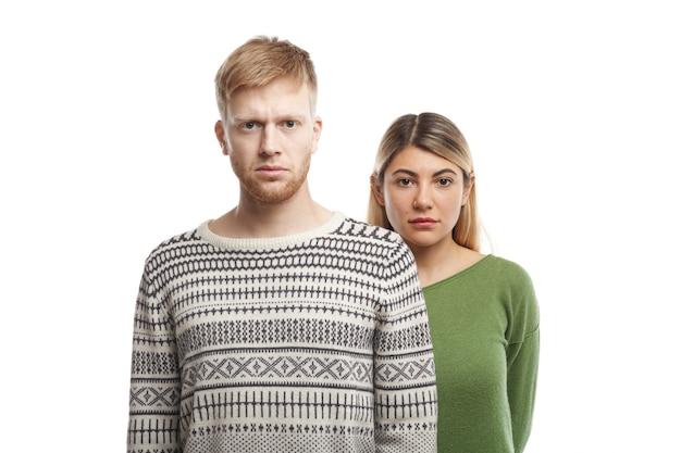 カジュアルな服を着てポーズをとって、深刻な表情をしている若い白人カップルの肖像画:セーターを着た彼女の無精ひげを生やしたボーイフレンドの後ろの白い壁に立っているブロンドの女性