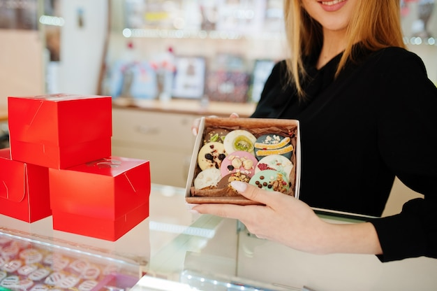 젊은 백인 여성 판매자의 초상화는 수제 쿠키와 과자를 들고 있습니다. 사탕 기념품 가게의 중소기업.