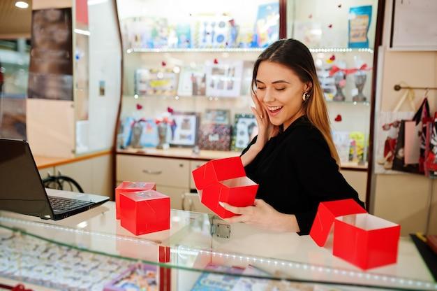 젊은 백인 여성 여성 판매자의 초상화는 빨간색 선물 상자를 들고 있습니다. 사탕 기념품 가게의 중소기업.