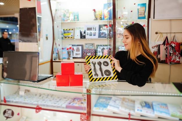 若い白人女性の売り手の肖像画は、チョコレートで作られたメカニックツールのセットを保持します。お菓子屋さんの中小企業。本物の男へのプレゼント。