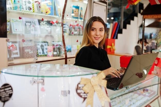 노트북을 사용하는 젊은 백인 여성 여성 판매자의 초상화. 사탕 기념품 가게의 중소기업.