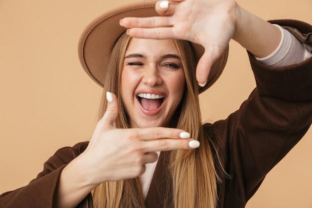 Портрет молодой кавказской девушки в шляпе и пальто, смеющейся и делающей жест портретной рамки, изолированный на бежевом