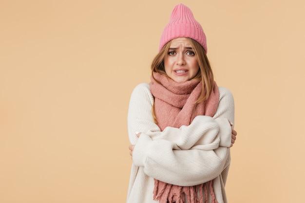 Портрет молодой кавказской девушки в зимней шапке и шарфе, дрожащей и холодной, изолированной на бежевом