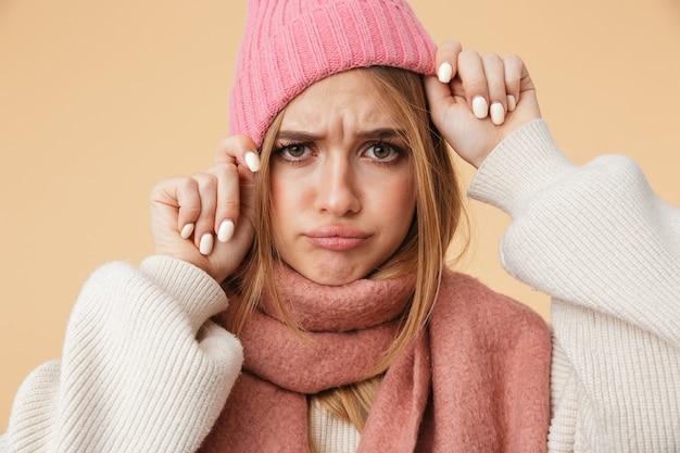 Портрет молодой кавказской девушки в зимнем шарфе, хмурящейся и касающейся ее шляпы, изолированной на бежевом