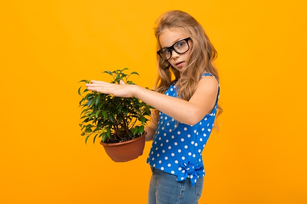 植物を保持している黒い眼鏡で長い金髪の若い白人の女の子の肖像画