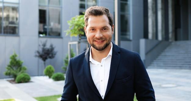 Портрет молодой кавказский красивый бизнесмен, стоя на открытом воздухе, повернувшись лицом к камере и весело улыбаясь. красивый мужчина в костюме улыбается на улице в городе.