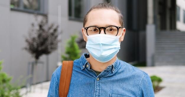 医療マスクを脱いで、屋外のカメラに微笑んで眼鏡をかけて若い白人ハンサムな男の肖像画。検疫の路上で陽気な男性。ズームアウトします。眼鏡とウイルス対策の男。