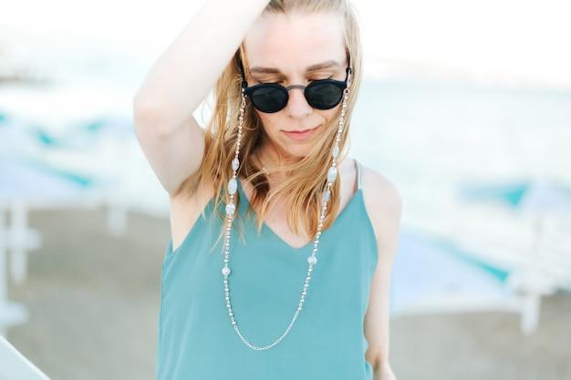 Портрет молодой кавказской смеясь над улыбающейся девушкой женщины в солнечных очках на открытом воздухе на фоне пляжа.