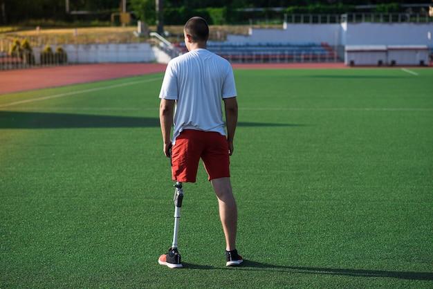 フィールド上のスタジアムに義足を持つ若い白人男性アスリートブルネットの肖像画。背面図。