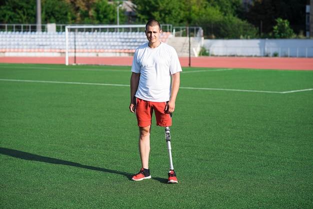 フィールド上のスタジアムに義足を持つ若い白人男性アスリートブルネットの肖像画