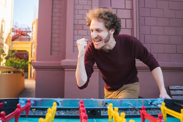 楽しんで、テーブルサッカーをしている若い白人男性の肖像画。