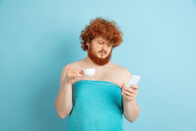 그의 아름다움의 날과 피부 관리 루틴에서 젊은 백인 남자의 초상화. 커피를 마시고 소셜 미디어를 보는 자연스러운 붉은 머리를 가진 남성 모델. 몸과 얼굴 관리, 자연, 남성 미용 개념.
