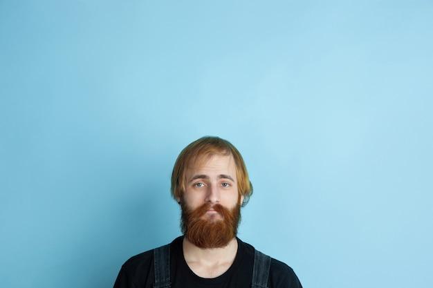 Портрет молодого кавказца выглядит мечтательным, милым и счастливым. глядя вверх и думая о синем пространстве