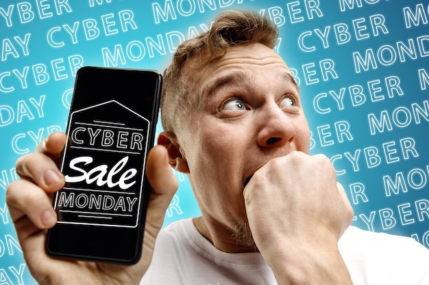 네온 글자와 함께 파란색 배경에 휴대 전화 화면을 보여주는 젊은 백인 남자의 초상화. 판매, 블랙 프라이데이, 사이버 월요일, 금융, 비즈니스의 개념. 온라인 상점 및 지불 청구서.