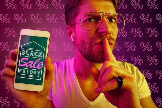 퍼센트와 보라색 배경에 휴대 전화 화면을 보여주는 젊은 백인 남자의 초상화. 판매, 블랙 프라이데이, 사이버 월요일, 금융, 비즈니스의 개념. 온라인 상점 및 지불 청구서.