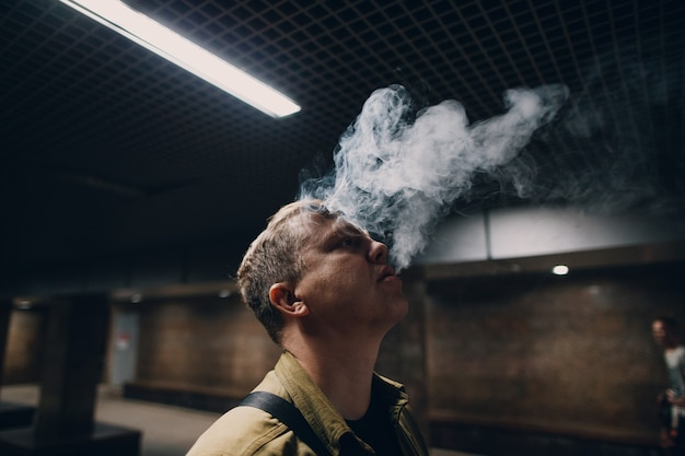 Портрет молодого кавказского человека, курящего электронную сигарету в темноте с линией света.