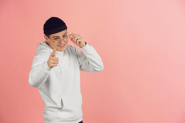 핑크 스튜디오 배경에 밝은 감정을 가진 젊은 백인 남자의 초상화