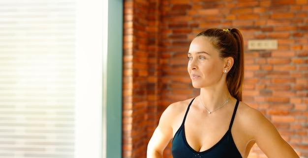 Портрет молодой кавказской красивой спортивной женщины фитнеса, отдыхающей и позирующей во время тренировок, глядя в сторону. .