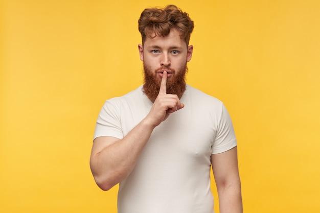 神経質で、指で沈黙のジェスチャーを示す大きな重い赤ひげを持つ若い白人赤毛の男の肖像画。